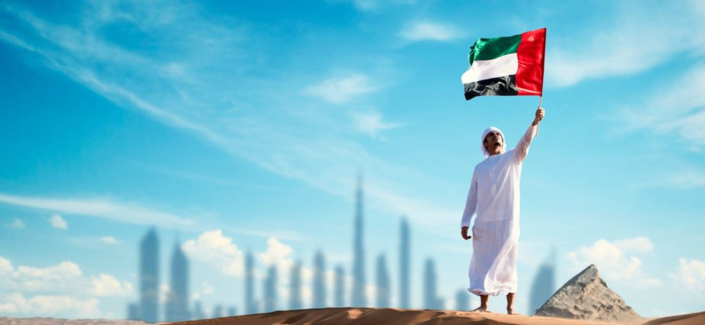 A man holding up the UAE flag with the Dubai skyline in the background.