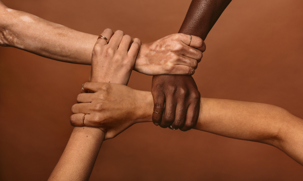 Hands of different ethnicities pictured together.