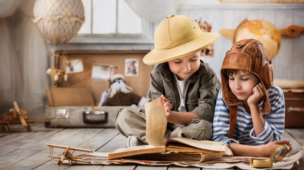 Two kids reading an old book.