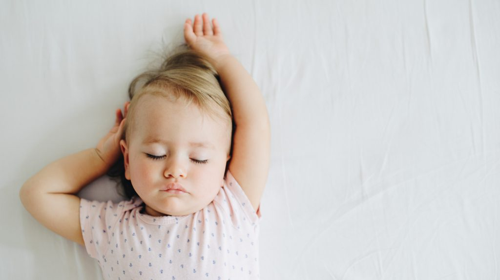 A baby sleeping on a white sheet.