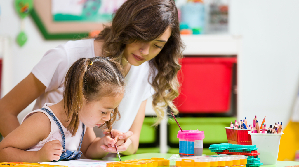 A teacher assisting a child to paint in a nursery.