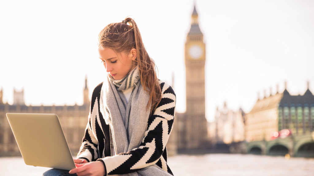 A girl with a laptop in front of the Big Ben in London.