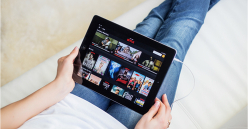 Image of person holding iPad streaming Netflix.